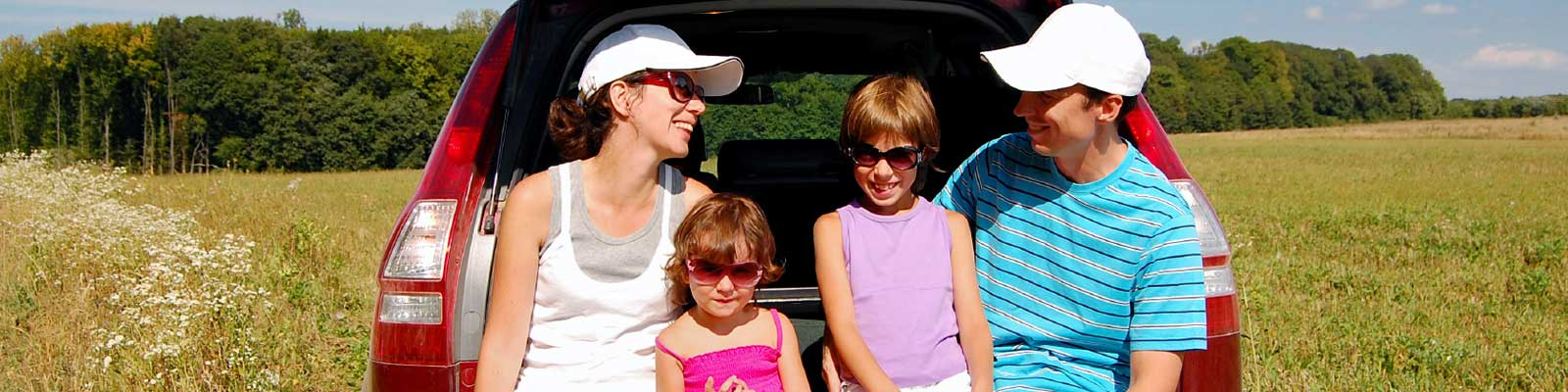 Family Sitting on the back of the car